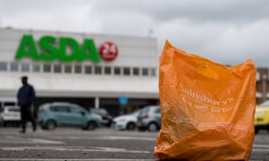 A Sainsbury's shopping bag in front of an Asda supermarket in London, England.