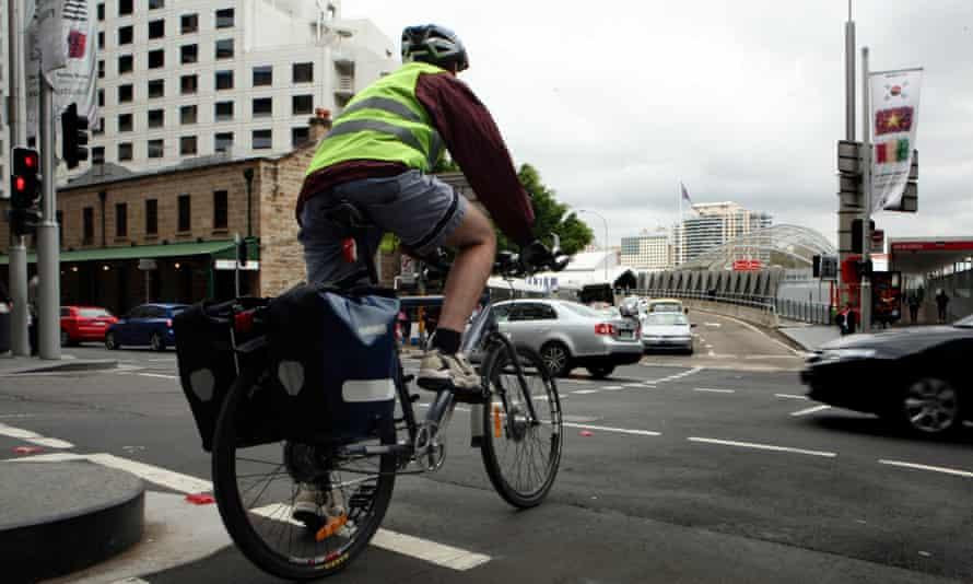 A cyclist rides through traffic in Sydney's city centre.