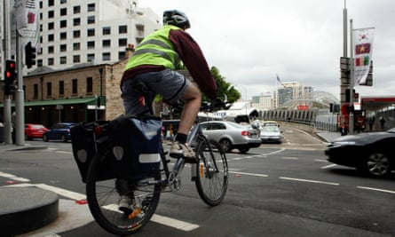 A cyclist rides through traffic in Sydney's city centre.