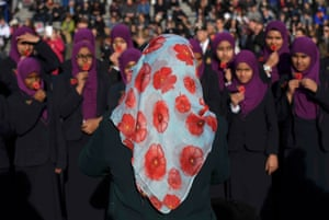 A teacher wears a poppy-themed headscarf as she photographs her pupils as they attend an Armistice Day event at Trafalgar Square in London