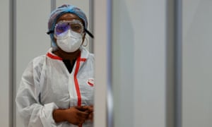 A health worker wearing protective gear waits for passengers to be tested for Covid-19 on arrival at Charles de Gaulle airport near Paris, France.