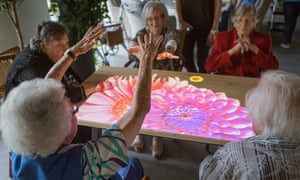 A group of women enjoy creating a blooming flower on the Tovertafel