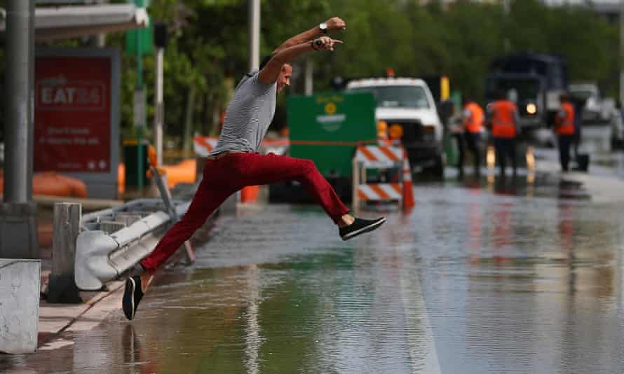 Michel Rodriguez tries to jump to a shallow spot as he crosses a flooded street in Miami Beach in 2015.