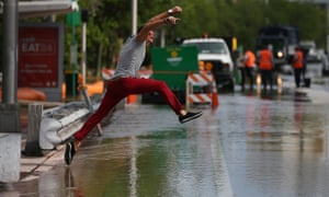 A man tries to jump to a shallow spot as he crosses a flooded street in Miami Beach, Florida, in September.