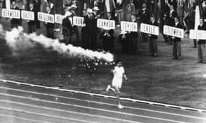 Australian athlete Ron Clarke, holder of the junior mile record, carries the Olympic torch into the stadium during the opening ceremony of the 1956 Olympic games in Melbourne.