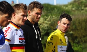 Mark Cavendish of Great Britain (right) and fellow Tour de France riders observe a minute's silence at a war memorial
