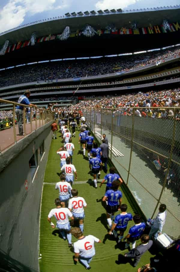The teams take to the field of the Azteca Stadium.