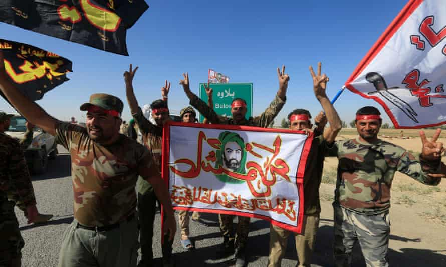 Shia Popular Mobilisation Forces members celebrate on the outskirts of Kirkuk on Tuesday.
