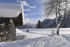 Two woman make their way through the fresh snow in Lofer, Austria