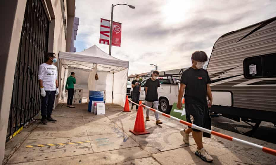 A woman self-tests for coronavirus as people wait their turn at a Covid-19 mobile testing site in Los Angeles, California, at the weekend as the US set a record for new daily cases.
