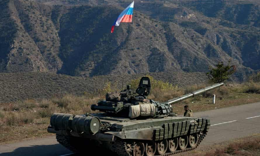 A service member of the Russian peacekeeping troops stands next to a tank in Nagorno-Karabakh.