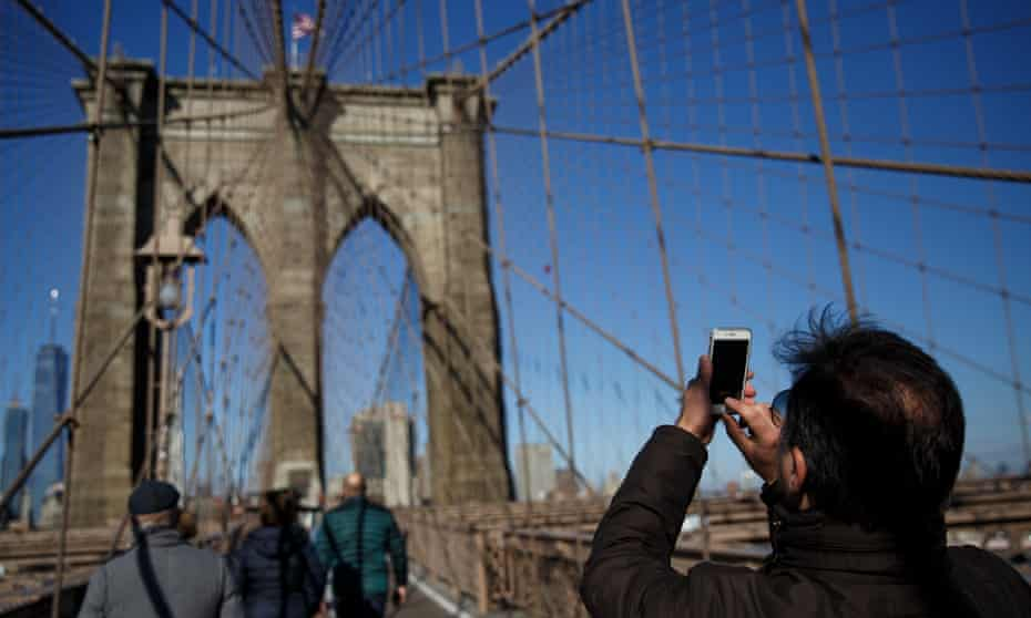 A man takes a photograph on the Brooklyn bridge. New York City is ranked No 1 in Instagram's most-geotagged cities of the year.