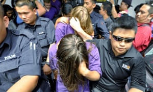 Eleanor Hawkins (front) and three other tourists from Canada and the Netherlands are escorted by police as they leave a court hearing in Kota Kinabalu on Wednesday.