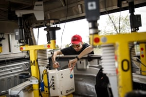 Hunter Anderson, a meteorology student at St. Cloud State University and currently an intern with the Center For Severe Weather Research, inspects and prepares tornado pods in a scouting vehicle. The tornado pods are heavy metal discs with instruments that measure and map winds at ground level.