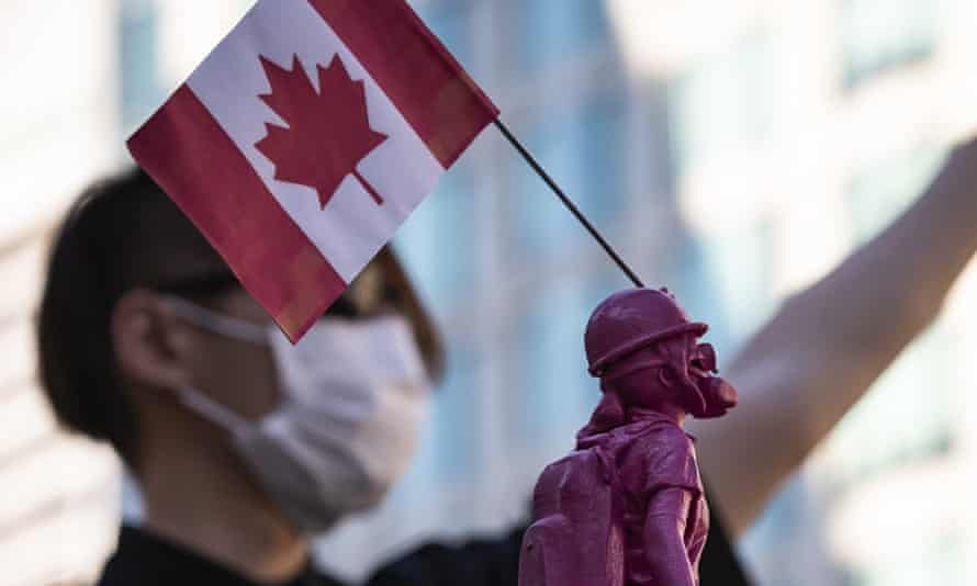 A democracy movement supporter holds a Lady Liberty Hong Kong statuette with a Canadian flag during a rally in Vancouver, British Columbia.