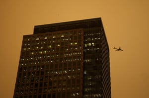 A plane flies past buildings in the Canary Wharf district as the sky turns red as dust from the Sahara carried by storm Ophelia filters sunlight over London