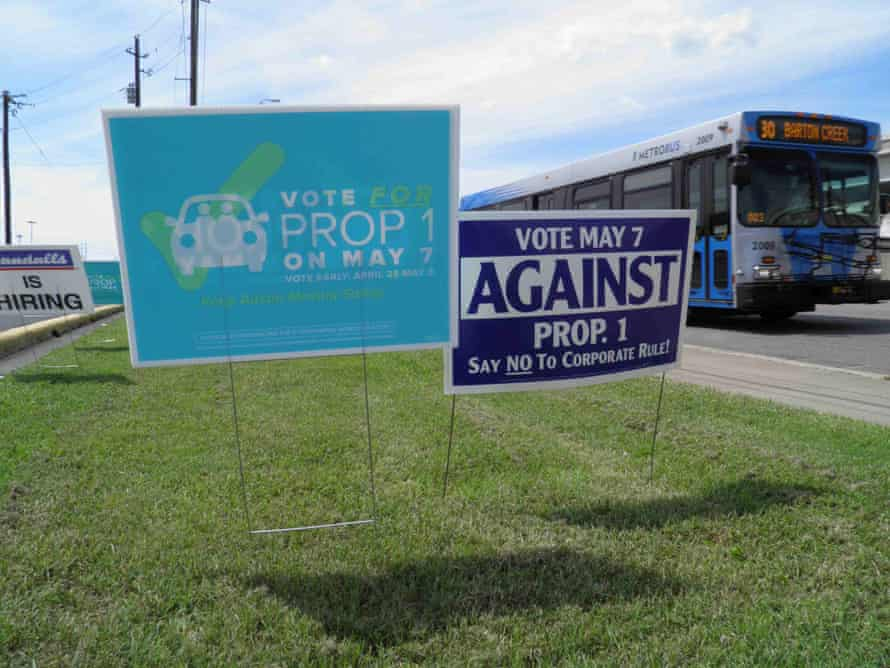 Campaign signs concerning the Austin vote over fingerprint requirements for Uber and Lyft.