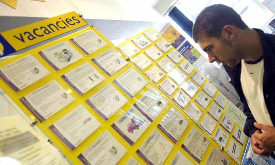 a man looks at a vacancies board