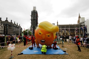 People inflate a balloon depicting Donald Trump as an orange baby in London, England