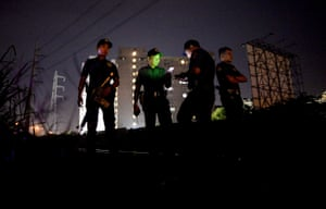 Police officers stand guard near a crime scene where a suspected drug pusher was shot dead in Manila