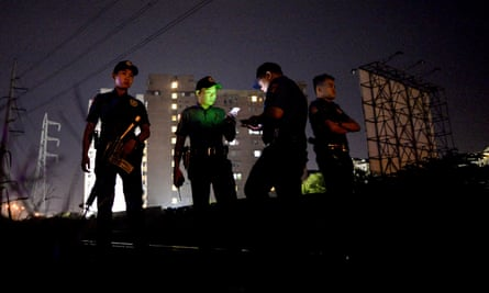 Police officers stand guard near a crime scene where a suspected drug pusher was shot dead in Manila.