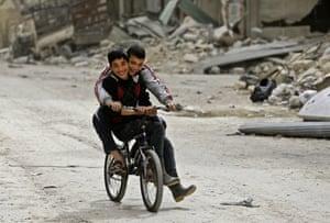 Boys ride a bike in al-Shaar, an area formerly held by rebels