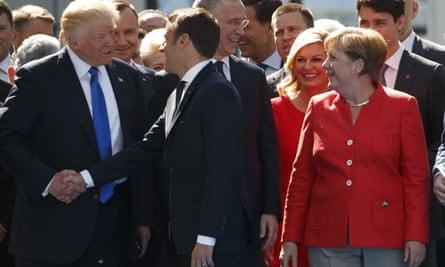 Angela Merkel watches as Donald Trump shakes hands with Emmanuel Macron in Brussels