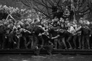 Sport – singles, first prize. Competitors from the Up'ards and Down'ards teams reach for the ball during the annual Royal Shrovetide football match in Ashbourne, Derbyshire, England