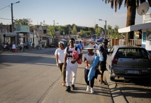 Township resident and yoga teacher, Sindiso Moyo (C) walks to class with fellow Yoga4Alex teacher, Bongekile Nguza (L) and friends