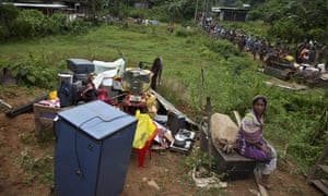 A woman sits with her belongings after forest officers demolished her house during an eviction drive on the outskirts of Gauhati, India in August 2017
