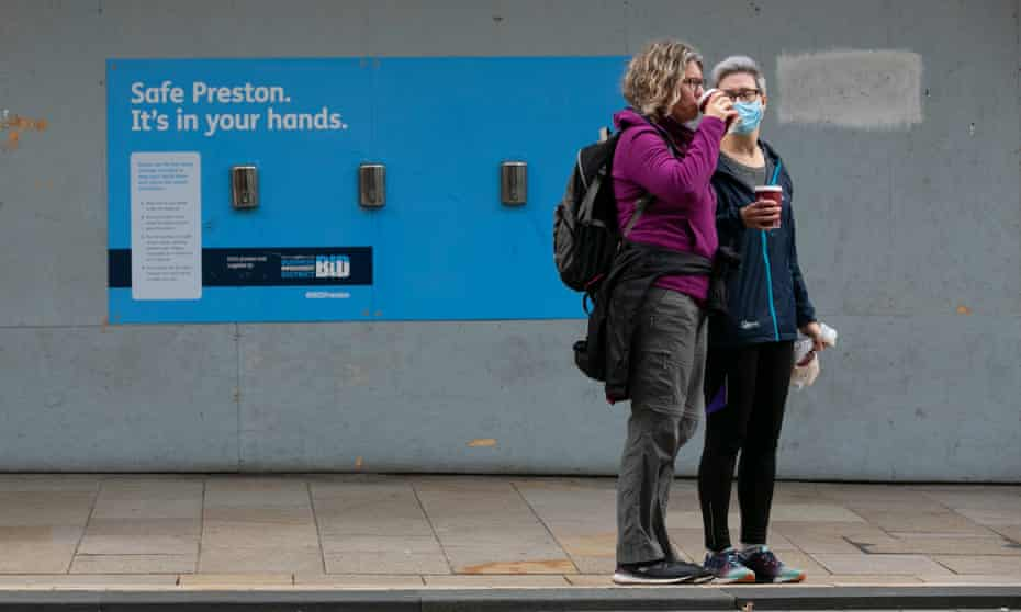 Women drink coffee in front of a hand-sanitising station in Preston, Lancashire.