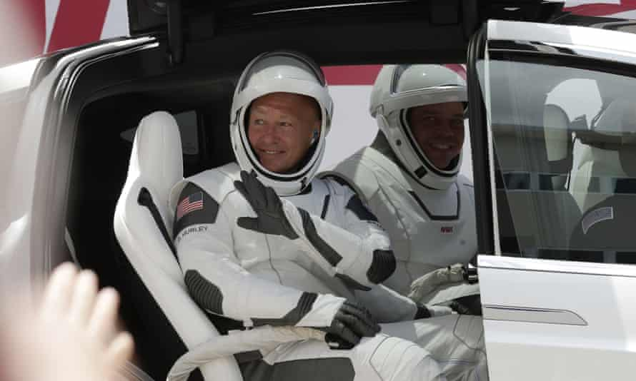 Nasa astronauts Douglas Hurley, left, and Robert Behnken wave while seated in a Tesla SUV on their way to Pad 39-A, at the Kennedy Space Center in Cape Canaveral.