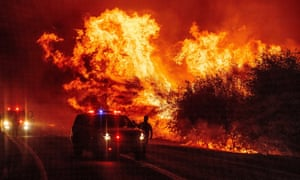 A law enforcement officer watches flames launch into the air as fire continues to spread at the Bear fire in Oroville, California, on Wednesday.