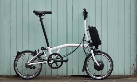 An electric Brompton standing against pale blue wooden cladding