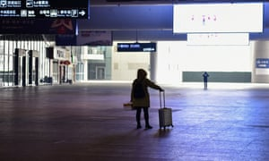 A passenger stands after arriving at the nearly-deserted Wuhan train station, usually full of passengers ahead of the Lunar New Year, in Wuhan on January 23