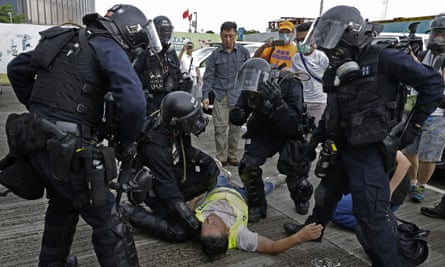 A cameraman lies injured after riot police fire tear gas on protesters outside the Legislative Council, in Hong Kong, on 12 June 2019.