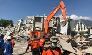 Indonesian rescuers work on the collapsed hotel Roa Roa as they try to find survivors in Palu