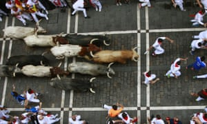 Bulls from the Cebada Gago ranch chase runners (mozos) at the San Fermín festival in Pamplona, northern Spain.