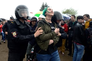 Police officers remove a participant from an unauthorised protest in central St Petersburg