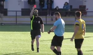 A masked man brandishes a red card