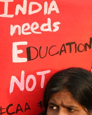 Woman with a sign saying 'India needs education not #CAA'