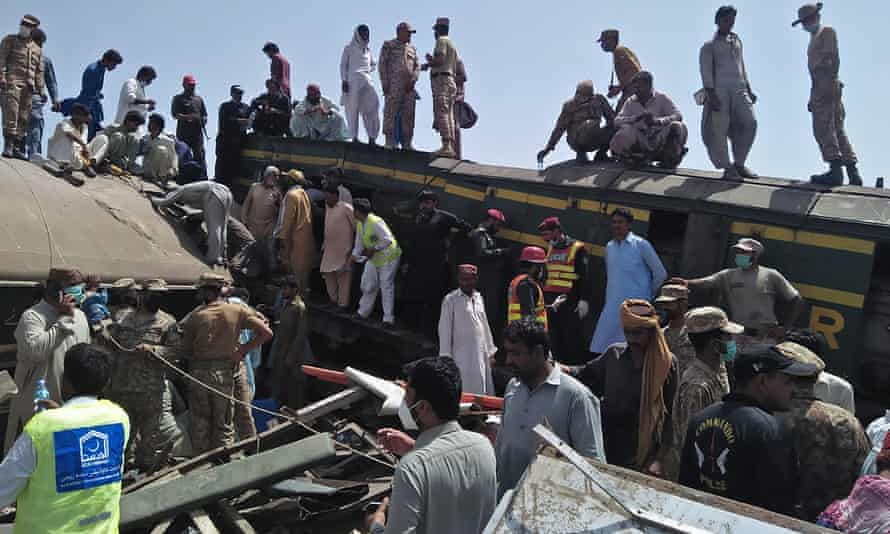 Soldiers and volunteers work at the site of a train collision in Ghotki district in southern Pakistan where two express trains collided on Monday, killing dozens of passengers