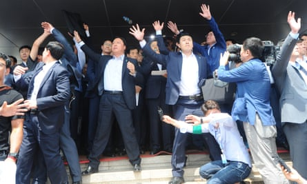 Security officers try to protect South Korean prime minister Hwang Kyo-ahn from bottles and eggs thrown by angry residents in Seongju.