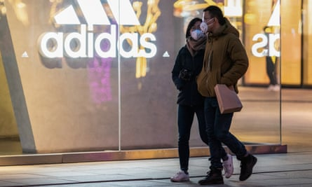 People in masks walk past an Adidas sign in Beijing