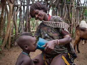Dile Bokoro (39) gives fresh goat's milk to her son.