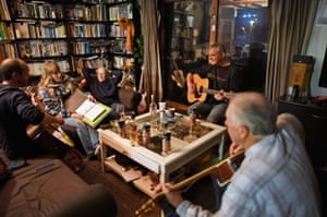 Residents play music and enjoy drinks at a late night gathering