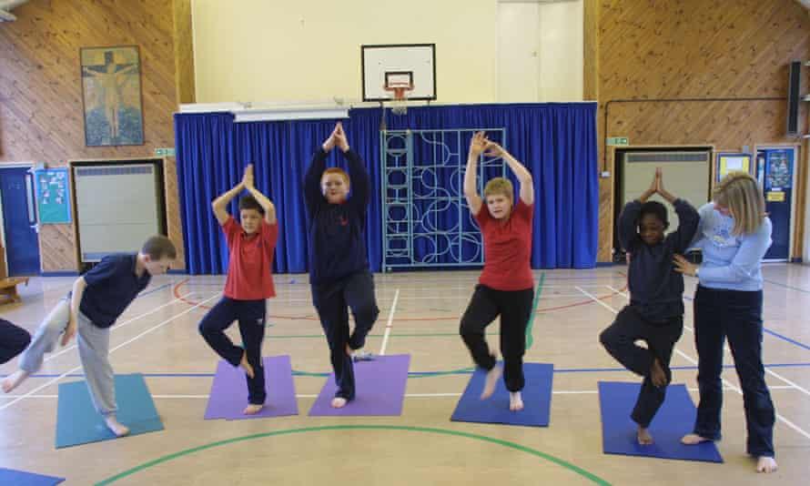 Children attend a school yoga class.