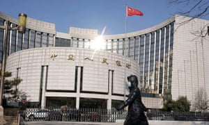 A woman wearing a mask walks past the headquarters of the People's Bank of China, the central bank, in Beijing, China.