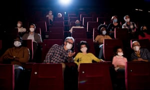 A movie audience dons masks.