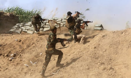 Iraqi Sunni fighters battling Islamic State jihadists alongside government forces fire their weapons on the outskirts of Iraq's Baiji oil refinery.